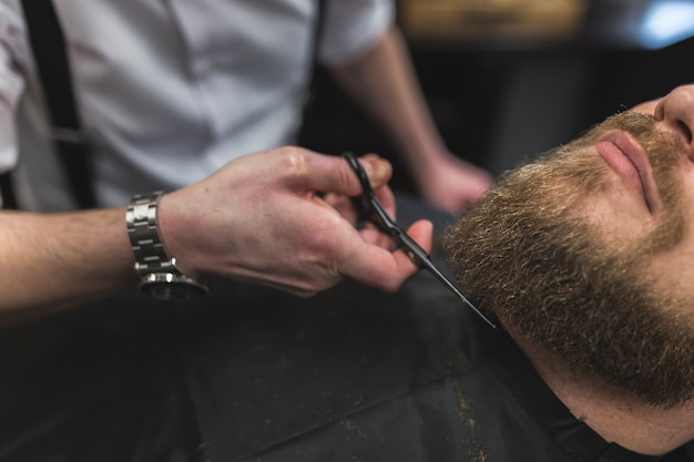 Barber cutting beard of crop client