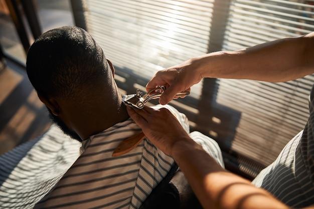 ポータブルバリカンでクライアントの髪をカットする理髪店