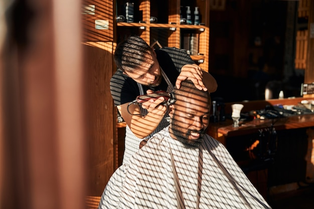 プロの電動バリカンでクライアントの髪をカットする理髪店