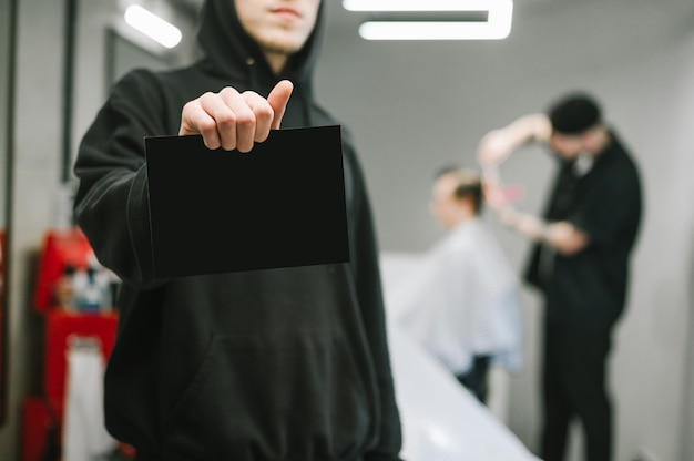 Barber in dark hoodie holds a card for copyspace in a male hairdresser and barber clipping clients