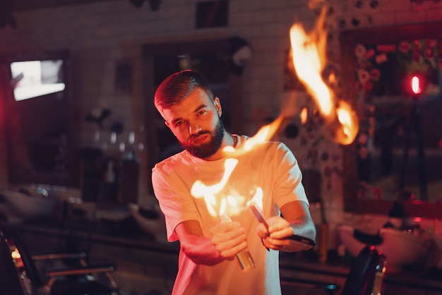 Barber demonstrates fire for haircut with hot scissors