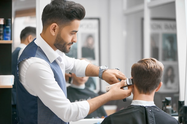 Barber doing new haircut for young client sitting in front of mirror.
