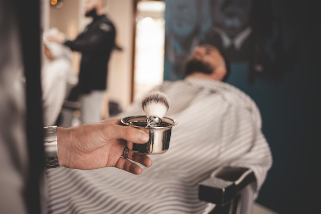 Barber holding in his hand a brush for shaving