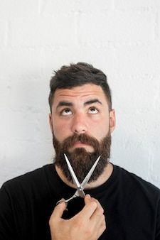 Barber holding professional scissors near beard at barbershop