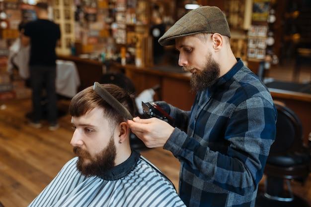 Парикмахер держит расческу и стригет клиенту волосы. профессиональная парикмахерская - модное занятие. мужской парикмахер и клиент в парикмахерской в стиле ретро