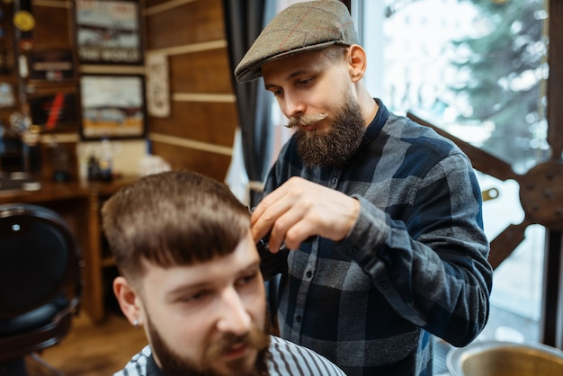 Парикмахер держит расческу и стригет клиенту волосы. профессиональная парикмахерская - модное занятие. мужской парикмахер и клиент в салоне в стиле ретро