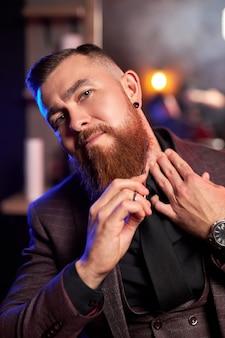 Парикмахер в парикмахерской сам бреет бороду ножницами