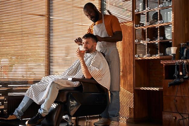はさみでクライアントの髪を切るエプロンの床屋