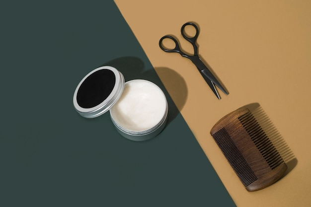 Barber kit with comb, scissors and wax on green and brown background