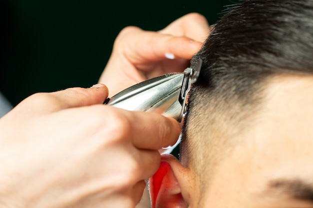 Barber makes haircut with cutting machine