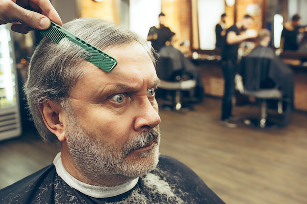 Barber making haircut attractive old man in barbershop