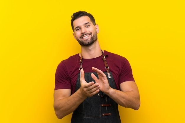 Barber man in an apron applauding