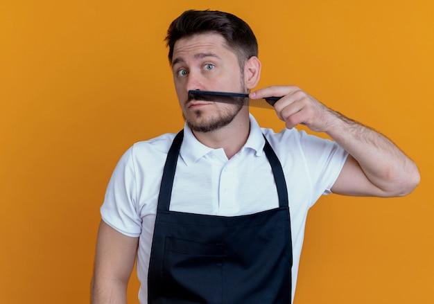 Uomo del barbiere in grembiule che pettina la sua barba che guarda l'obbiettivo in piedi su sfondo arancione
