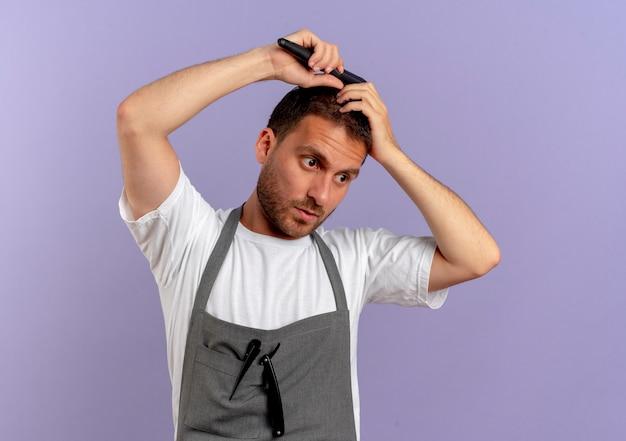 Uomo del barbiere in grembiule che pettina i capelli con la faccia seria in piedi sopra il muro viola
