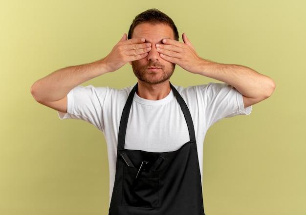 Uomo del barbiere in grembiule che copre gli occhi con le mani in piedi sopra la parete chiara