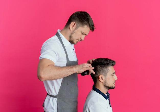 Uomo barbiere in grembiule che taglia i capelli con la macchina per il taglio dei capelli del cliente soddisfatto sul muro rosa