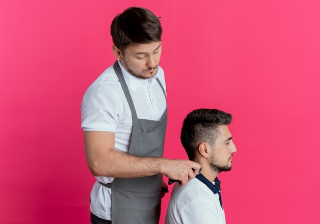 Barber man in apron cutting hair with hair cutting machine of satisfied client over pink wall