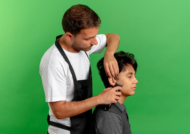 Barber man in apron cutting hair with scissors of satisfied client standing over green wall 2