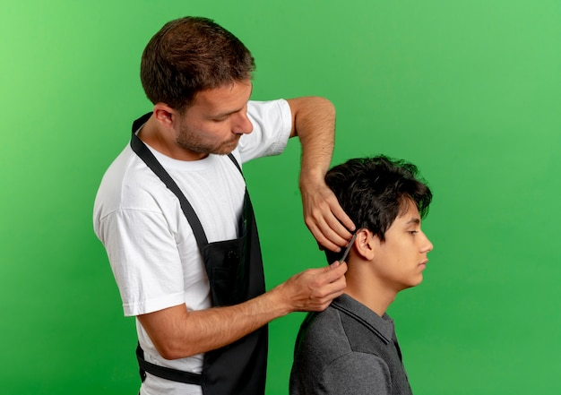 Barber man in apron cutting hair with scissors of satisfied client standing over green wall