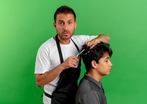 Uomo del barbiere in grembiule che taglia i capelli con le forbici del cliente soddisfatto in piedi sopra la parete verde