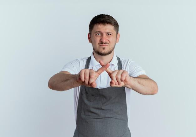 Barbiere uomo in grembiule dispiaciuto che mostra il segnale di stop incrociando le dita indice in piedi sul muro bianco