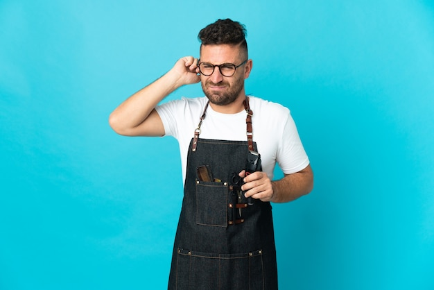 Barber man in an apron frustrated and covering ears