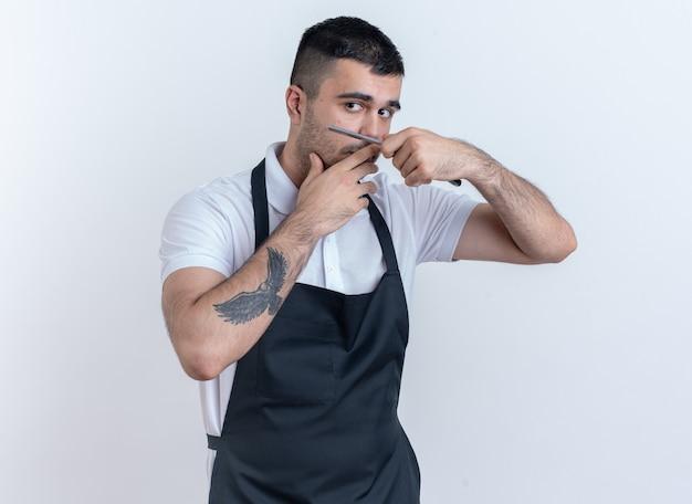 Uomo del barbiere in grembiule che va a radersi tenendo il rasoio che sembra fiducioso in piedi sopra il bianco