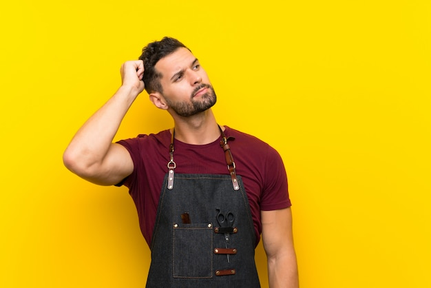 Barber man in an apron having doubts and with confuse face expression