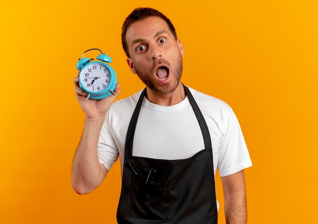 Barber man in apron holding alarm clock looking to the front worried with wide open mouth standing over orange wall