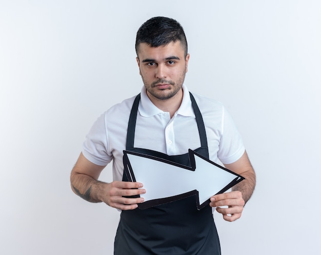 Barbiere in grembiule con freccia che guarda la telecamera con un'espressione seria e sicura di sé in piedi su sfondo bianco