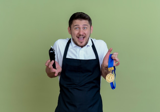 Barber man in apron holding beard trimmer and gold medal looking at camera excited and happy standing over green background