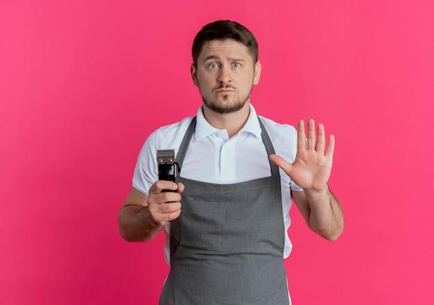 Barbiere uomo in grembiule tenendo la barba trimmer che mostra il segnale di stop con la mano aperta in piedi sopra il muro rosa