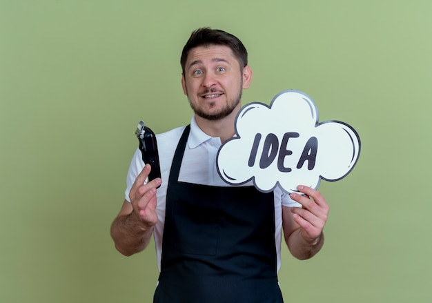 Barber man in apron holding beard trimmer and speech bubble sign idea word  with happy face standing over green wall