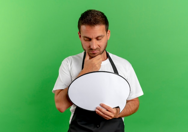 Barber man in apron holding blank speech bubble sign looking at it with pensive expression thinking standing over green wall