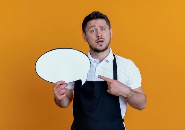 Uomo del barbiere in grembiule che tiene il segno di bolla di discorso in bianco pointign con il dito ad esso con espressione confusa in piedi sopra il muro arancione