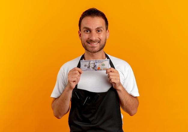 Uomo del barbiere in grembiule che tiene contanti guardando in avanti con il sorriso sul viso in piedi sopra la parete arancione