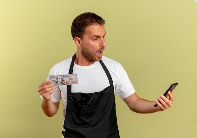 Uomo del barbiere in grembiule che tiene contanti guardando lo schermo del suo telefono cellulare sorpreso e stupito in piedi sopra la parete chiara