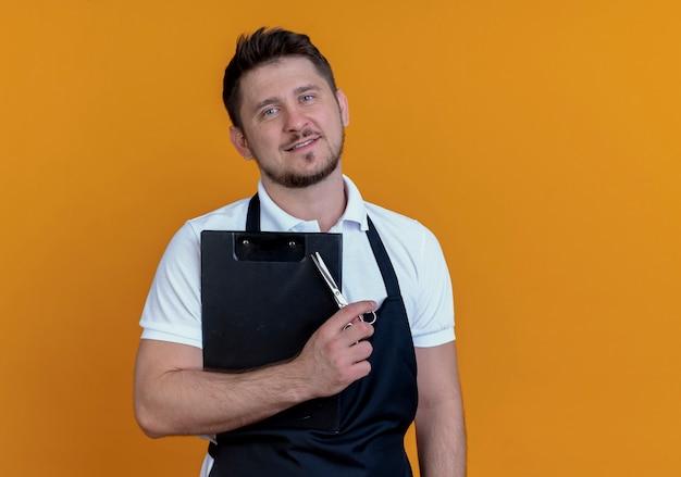 Uomo del barbiere in grembiule che tiene appunti e forbici che guarda l'obbiettivo con il sorriso sul viso in piedi su sfondo arancione