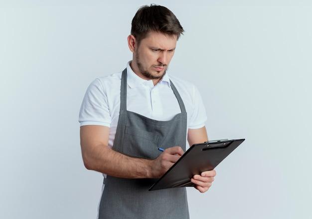 Uomo del barbiere in grembiule che tiene appunti scrivendo qualcosa con la faccia seria in piedi su sfondo bianco