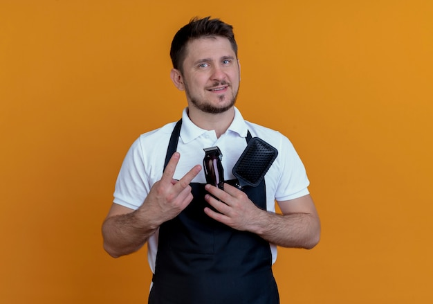 Barber man in apron holding hair brush and beard trimmer  with smile on face showing number two standing over orange wall