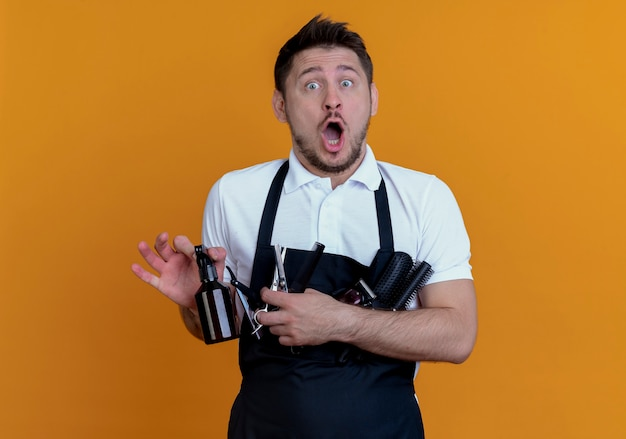 Barbiere uomo in grembiule azienda spazzole per capelli, spray e forbici guardando la telecamera sorpreso in piedi su sfondo arancione
