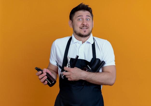 Barbiere in grembiule con spazzole per capelli, spray e forbici sorridente confuso in piedi sopra il muro arancione