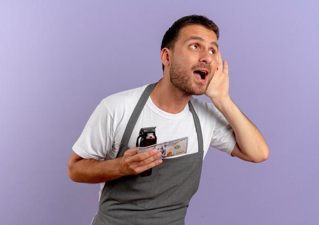 Uomo del barbiere in grembiule che tiene macchina per tagliare i capelli e contanti tenendo la mano vicino al suo orecchio cercando di ascoltare in piedi sopra il muro viola