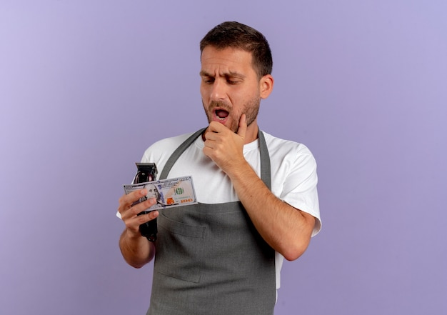 Barber man in apron holding hair cutting machine and cash loking amazed and surprised standing over purple wall