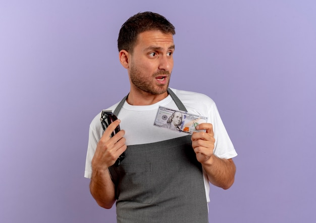 Barber man in apron holding hair cutting machine and cash looking aside confused standing over purple wall