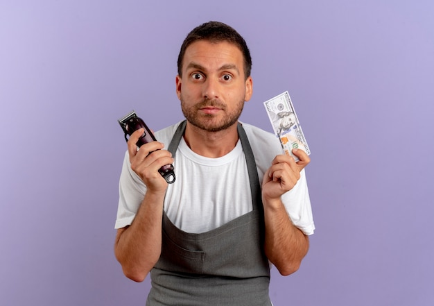 Barber man in apron holding hair cutting machine and cash looking to the front surprised standing over purple wall