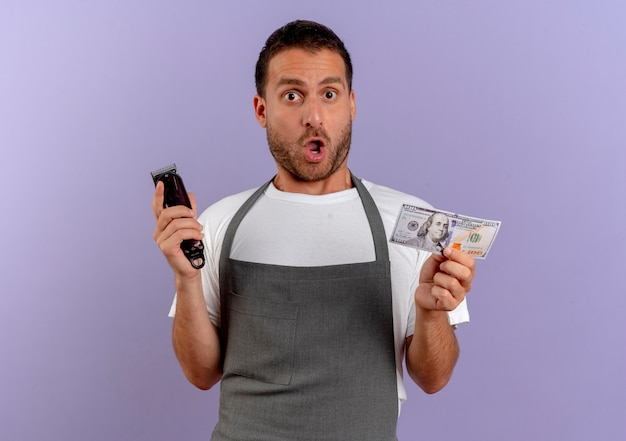 Barber man in apron holding hair cutting machine and cash looking surprised and amazed standing over purple wall