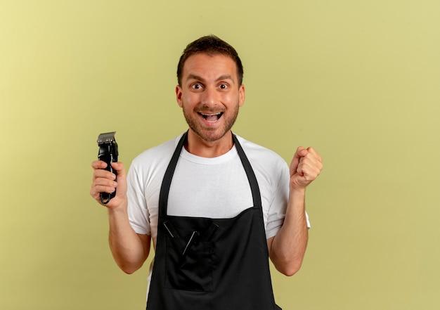 Uomo del barbiere in grembiule che tiene macchina per il taglio dei capelli stringendo il pugno felice ed eccitato in piedi sopra il muro di oliva