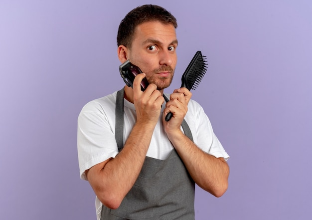 Barber man in apron holding hair cutting machine and hair brush looking to the front confused standing over purple wall