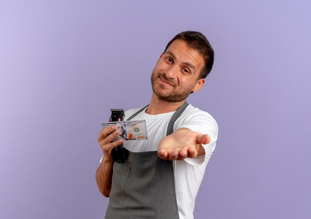Barber man in apron holding hair cutting machine holding hand in front of himself asking for money standing over purple wall